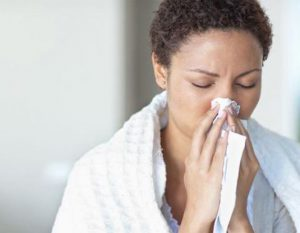 Woman with cold symptoms clearing her nose